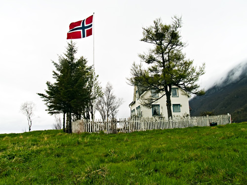 House in field flying norwegian flag